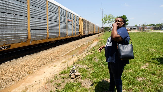 Melissa McCullough, cousin of Ernestine Dixon, visits the tracks where Dixon was struck by a train in the Southernside community on Wednesday, May 9, 2018.