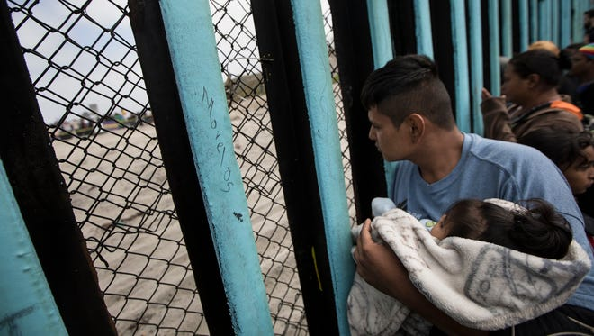 In this April 29, 2018 file photo, a member of the Central American migrant caravan, holding a child, looks through the border wall toward a group of people gathered on the U.S. side, as he stands on the beach where the border wall ends in the ocean, in Tijuana, Mexico, Sunday, April 29, 2018.