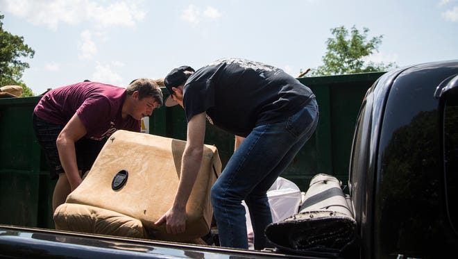 Nate and Caleb Rey, brothers from Beaverdale, toss flood damaged furniture into a dumpster at Beaverdale Park on Tuesday, July 3, 2018, in Des Moines. Dumpsters, placed in five locations by the city filled up quickly leaving people to wait in long lines to empty their trucks and cars.