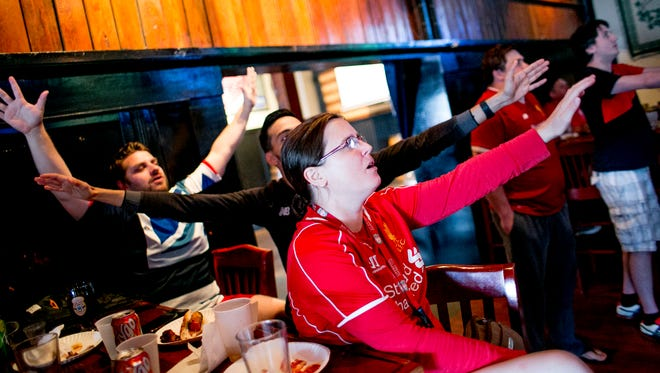 "Amy Gilley, 37, of Ypsilanti sings ""You'll Never Walk Alone"" before a Liverpool Football Club match at Thomas Magee's in Detroit on July 22."