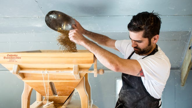 David Bauer pours grains into his Austrian-made mill.