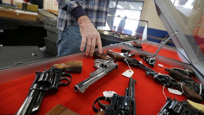 A dealer arranges handguns in a display case in advance of a show at the Arkansas State Fairgrounds in Little Rock on Friday. Arkansas gun advocates in the Legislature are supporting bills that would permit firearms on university campuses, expanding citizens' rights to use deadly force and other efforts.