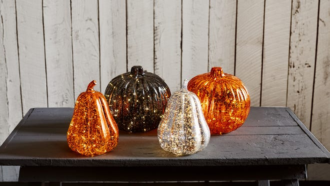 LED lights illuminate an array of mercury glass and resin pumpkins for a festive Halloween without dealing with the mess of carving.