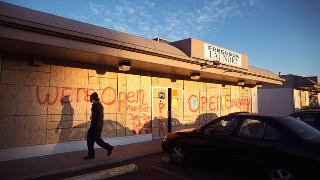 Plywood covers the glass front of a strip mall along West Florissant Street on Nov. 14, 2014, in Ferguson, Mo. Many businesses along West Florissant are boarded up as residents prepare for the grand jury decision in the shooting death of Michael Brown.