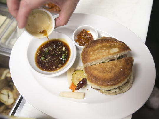 "Bob Tam, Executive Chef and Partner at Bitter & Twisted Cocktail Parlour, puts dipping sauce for the ""Dragon"" Dumpling Burger at Bitter & Twisted Cocktail Parlour in Phoenix."