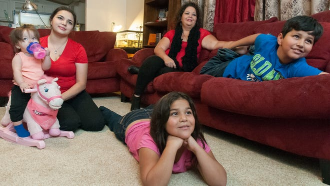 Marietta Valdez, center background, enjoys family time in her new home with her granddaughter Kailani Rain, 10 months, left and children Lilly, 17, Alya, 8 and Christopher, 10.
