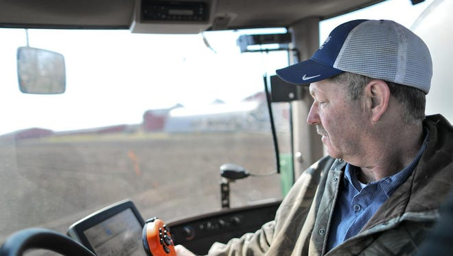 Custom farmer Bob Dorr keeps an eye on the monitor while spraying fertilizer and herbicide onto a tilled field near the family's farm in Avalon on Friday, April 27.