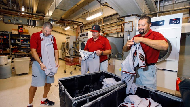 Clubhouse assistants (from left) Shawn Moore,  Jimmy Garrett and Lupe Uribe fold uniforms for the  Arizona Diamondbacks ' prior to their MLB game Tuesday, August 25, 2015 in Phoenix, Ariz.
