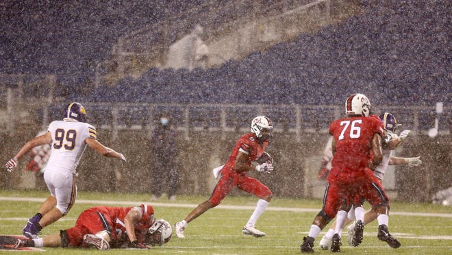 Xavier Black of McKinley picks up yardage during a downpour in their game against Jackson at McKinley on Friday, August 28, 2020. (CantonRep.com / Scott Heckel)\r