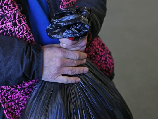 Hawkeye Morgan, 37, holds a bag of goods he and his wife recieved from volunteers at the annual Room at the Inn event in Turner, Ore. Volunteers served 120 area homeless during the event.
