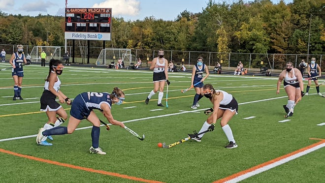 Quabbin's Alison Michalik (12) tries to send a centering pass by the stick of Gardner High's Hannah Goss during the second quarter of Monday afternoon's game at Watkins Field. Also pictured are Quabbin's Natalya Morin (5) and Jorji LaViolette (21) and Kylie Casey (26, far right) as well as Gardner's Rozeli Gonzalez (second from left), Emma Ashmore (17) and Skylar Grenier (23).