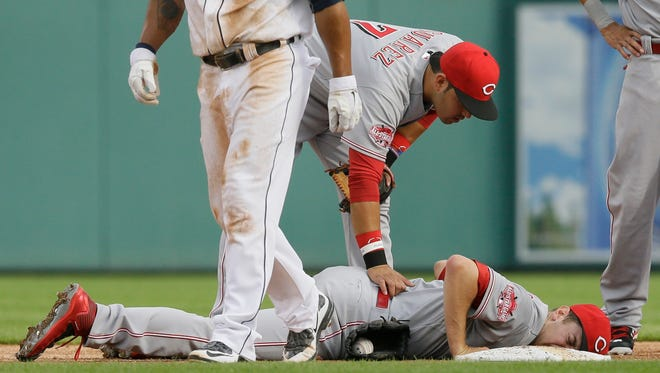 Cincinnati Reds starting pitcher Jon Moscot lies face-down on second after a tag of Detroit Tigers' Anthony Gose during a rundown in the first inning.
