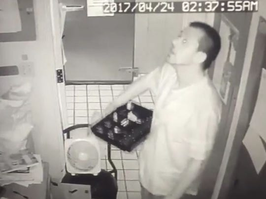 A burglar, identified by police as former Oscar's employee Chris Munje, is filmed by security cameras during a break-in at the restaurant on April 24. Munje has pleaded not guilty.