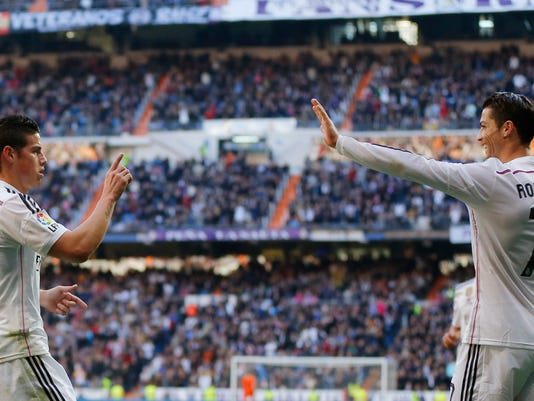 Real Madrid's James Rodriguez, left, celebrates his goal with teammate Cristiano Ronaldo, right, during a Spanish La Liga soccer match between Real Madrid and Espanyol at the Santiago Bernabeu stadium  in Madrid, Spain, Saturday, Jan. 10, 2015 . (AP Photo/Daniel Ochoa de Olza)