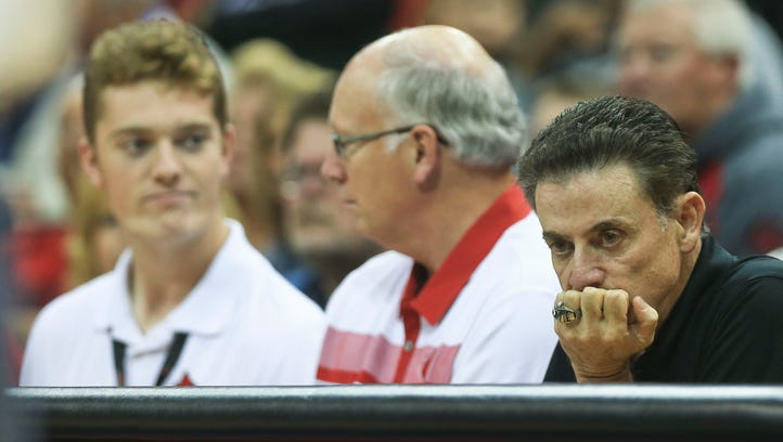 Louisville coach Rick Pitino stares down during a time