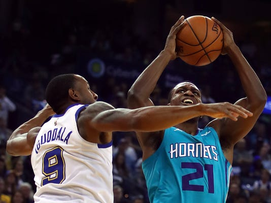 Charlotte Hornets' Treveon Graham, right, shoots against Golden State Warriors' Andre Iguodala (9) during the first half of an NBA basketball game Friday, Dec. 29, 2017, in Oakland, Calif. (AP Photo/Ben Margot)
