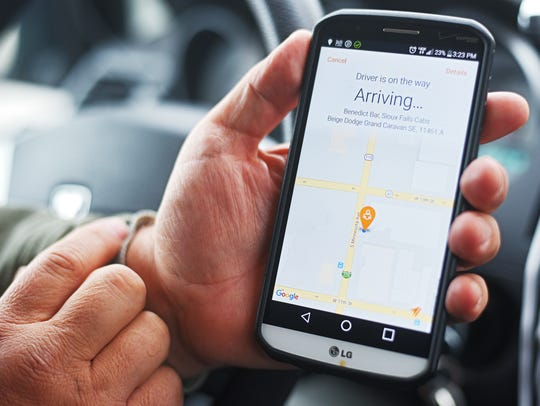 Sioux Falls Cab owner Benedict Bar shows off an ride-hailing app for his cab company, in this January 2017 file photo.