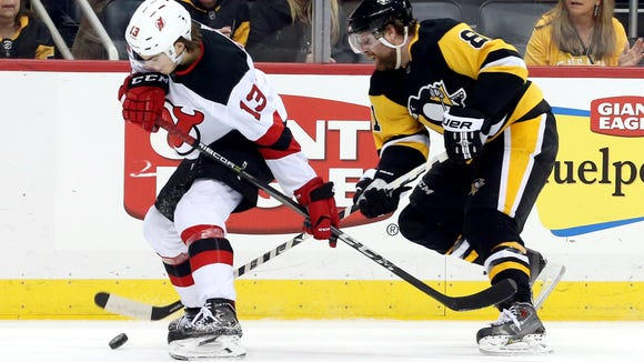New Jersey Devils center Nico Hischier (13) and Pittsburgh Penguins right wing Phil Kessel (81) chase the puck in overtime at PPG PAINTS Arena in Pittsburgh on March 23, 2018. The Devils won 4-3 in overtime.