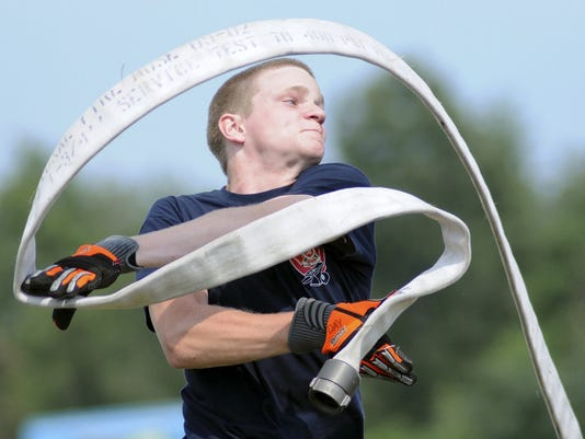 Firefighter Sam Day of the Annville-Cleona Fire District creates a frame for his body with a curling fire hose during the Firemen's Competition at the Lebanon Area Fair on Sunday.