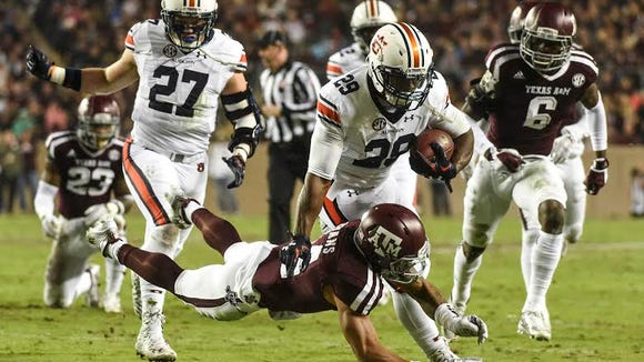 Jovon Robinson (29) pushes a defender off of him.  Auburn at Texas A&M in College Station, Texas. on Saturday, Nov. 7, 2015.