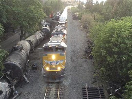 This photo taken from a drone, shows crumpled oil tankers lying beside the railroad tracks after a fiery train derailment on June 3 that prompted evacuations from the Columbia River Gorge town of Mosier. The derailment has state transportation officials asking for a halt to the massive trains because of concerns their heavier weight could be putting extra strain on a certain type of bolt that fastens the rails to the tracks.