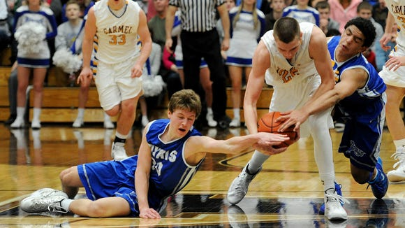 Carmel forward Zach McRoberts comes up with a loose ball between Hamilton Southeastern guard Eric Davidson, left, and forward Zach Gunn during the Class 4A Sectional #8 championship game, Saturday, March 8, 2014, at Noblesville High School. HSE won the game 50-42.