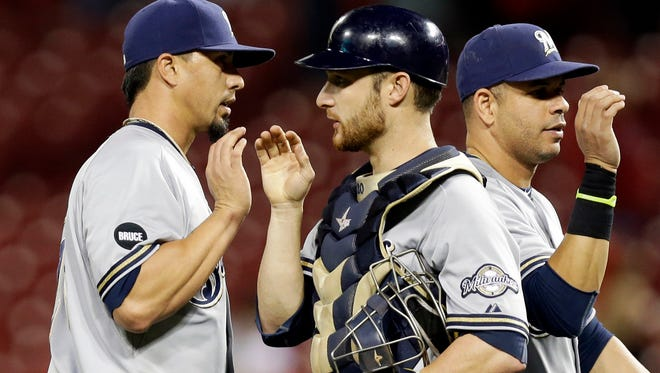 Milwaukee Brewers starting pitcher Kyle Lohse, left, is congratulated by catcher Jonathan Lucroy, center, after the Brewers defeated the Cincinnati Reds 5-0 in a baseball game, Wednesday, Sept. 24, 2014, in Cincinnati. (AP Photo/Al Behrman)