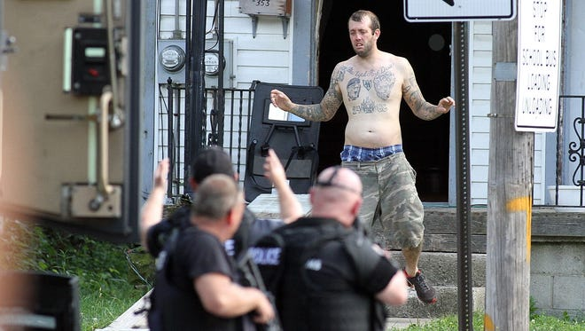 Ian Miller exits a house and into the custody of police SWAT team after a two hour stand-off on West Church Street on Thursday, Aug. 28, 2014. Miller told fire department EMT's responding to a call at 353 W. Church St. that he was armed and would shoot anyone who tried to enter, according to initial reports from police. Miller's mother and sister, as well as police negotiator Maj. Jeff Clewell talked to Miller over a cell phone for over an hour before he surrendered without incident at about 4:15 p.m.