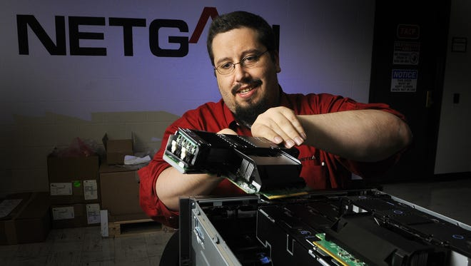 Jered Rassier, infrastructure team lead at Netgain, assembles a server rack in this 2011 file photo. Netgain recently made the Inc. 5000 list for the third year as one of America's fastest-growing companies.