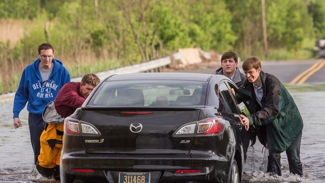 DNREC Secretary Colin O'Mara, right, State Senator Bryan Townsend, second right, and Minquas Fire Department responders Richard Thompson III, second left, and Brandon Hamm, center, help Brett Finnicum, left, remove his car from a flooded-out section of Airport Road in New Castle on Friday afternoon, May 16, 2014.