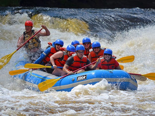 A group enjoys the the thrill of rafting through Piers Gorge on the Menominee River. The Menominee provides some of the best guided white-water rafting in the state.