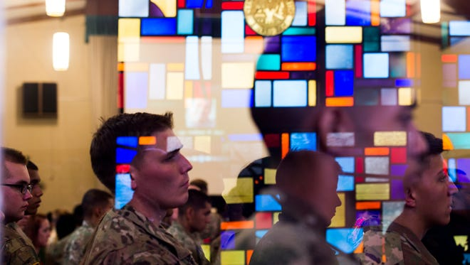Soldiers watching the casket with Sgt. William Bays carried down the aisle are reflected in the glass of the chapel on June 23, 2017.