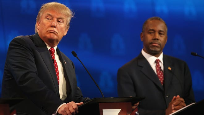 Presidential candidate Donald Trump pauses while Ben Carson  looks on during the CNBC Republican Presidential on Oct. 28.
