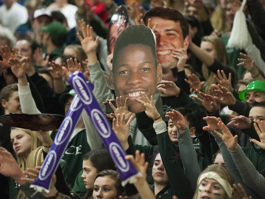 Rice fans hold up a photo of Ben Shungu during a free