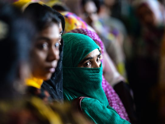 Bangladeshi travelers queue to collect tickets at a