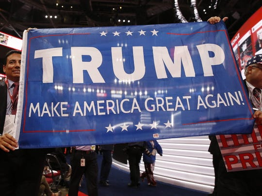 Delegates hold up a Trump banner on the floor during the first day of the 2016 Republican National Convention at Quicken Loans Arena in Cleveland, on July 18, 2016.