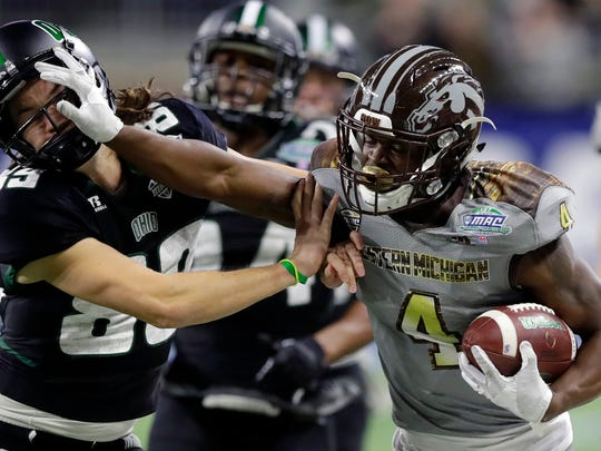 Western Michigan cornerback Darius Phillips (4) stiff-arms Michael Farkas (89) during the second half of the Mid-American Conference championship NCAA college football game, Friday, Dec. 2, 2016, in Detroit.