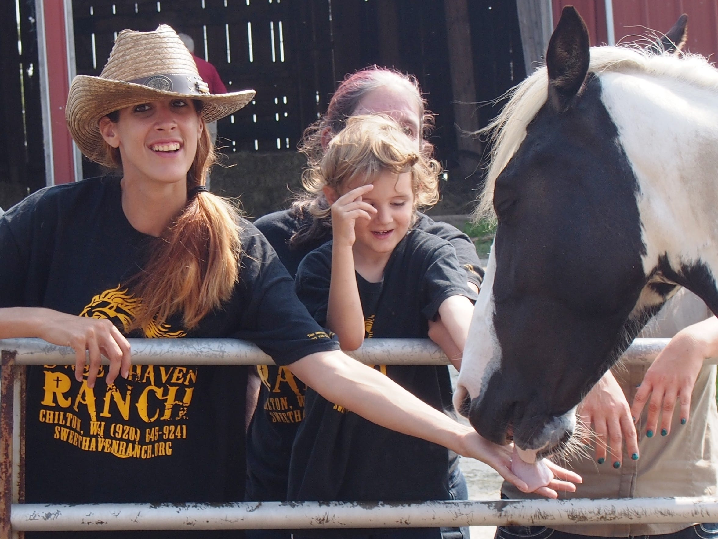 Valentine licks the hand of Desiree Doty, one of the ranch's volunteers.