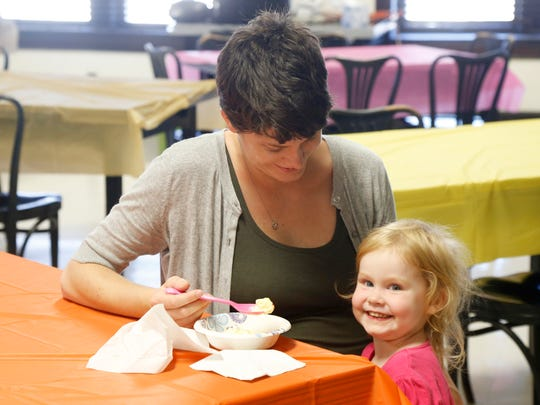 Interim director of Your Home Public Library in Johnson City , Natassia Enright feeds her daughter, Tamsin after a successful ice cream social held on July 13.