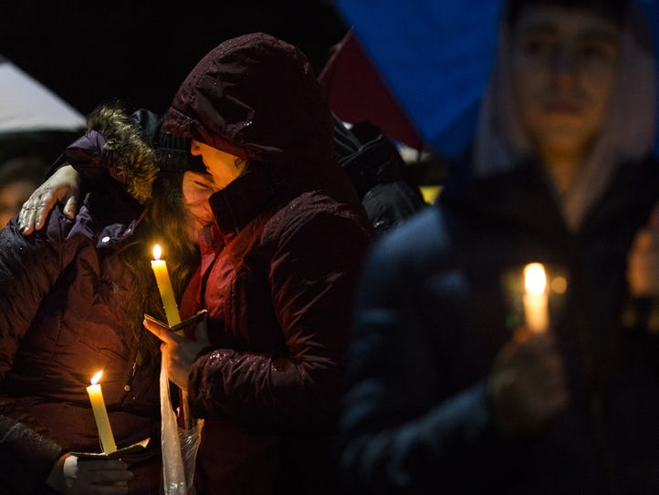 Mourners listen while names are read aloud during a