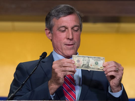 Gov. John Carney shows the $10 bill that he would use to bet on the Philadelphia Phillies vs. Chicago Cubs game during a press conference before Delaware's single-game sports betting began at Dover Downs Hotel & Casino in Dover on June 5, 2018.