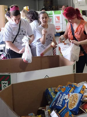 Volunteers sort through food stuffs and place them in bins during the 2014 food drive.