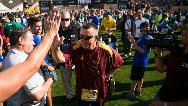 ASU football head coach Todd Graham greets fans and fellow runners during the 11th Annual Pat's Run Saturday, April 25, 2015 in Tempe, Arizona. 30,000 runners attended Pat's Run this year, breaking the record for the highest attendance during the run's history.
