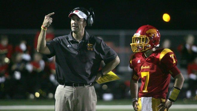 Carlisle head coach Mark Hoekstra confers with junior quarterback Jordan Pierce during a Sept. 26 home game against Ballard.