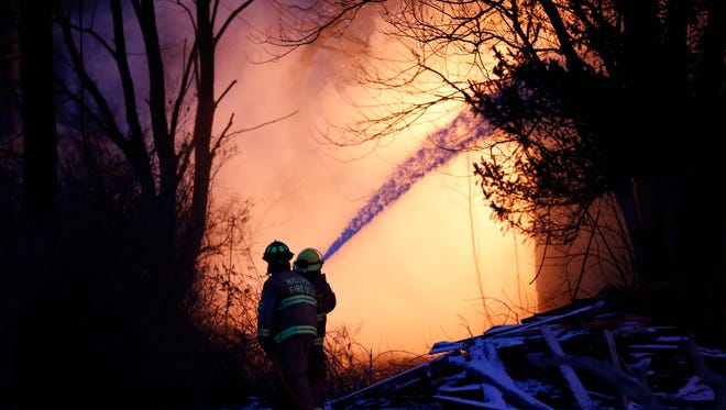 Firefighters hose done flames shooting out from a home at 34 Lee Street in the Town of Veteran Friday.