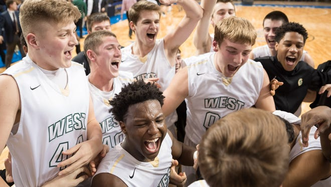 The West High Trojans celebrate a 50-30 victory over Iowa City City High at the US Cellular Center in Cedar Rapids Mar. 1, 2016.