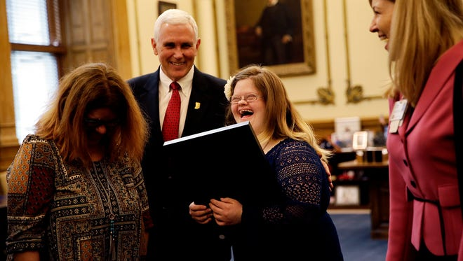 Gov. Mike Pence presents Mickey Deputy with the Sagamore of the Wabash inside his office at the Indiana State House on April 11, 2016. Jenny and Michael, Mickey's mother and father, and Brad, her brother, as well as her grandparents Gil and Linda Deputy and Joann Bennett stood by her as she received the state's highest civilian honor.