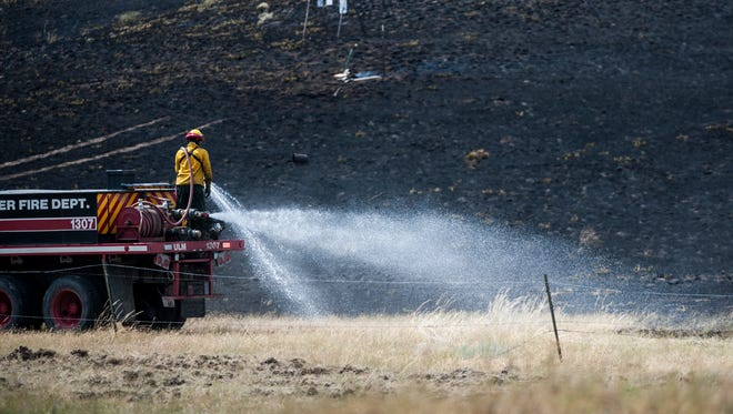 An Ulm volunteer firefighter sprays water on the edge of a grass fire at the Great Falls Shooting Sports Complex after a ricochet landed in a nearby wheat field Saturday, July 23, 2016.