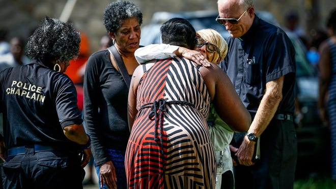 Tears roll down the face of Kathy Taylor, grandmother of one of the deceased persons found dead in an alleyway off of 30th street on the city's eastside, as she gets a hug after a prayer with IMPD Chaplain Holman on Sept. 14, 2016.