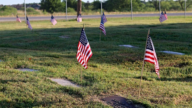 In this file photo, dozens of flags adorn the gravesites of veterans for Memorial Day at the Crestview Memorial Park cemetery.